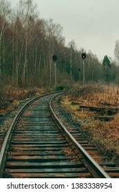Beautiful railway landscape, turn of the road. Unused railroad line in the forest. Cargo line, autumn nature. Tall traffic-lights with stop signals, passenger station. Desolate place, nobody around