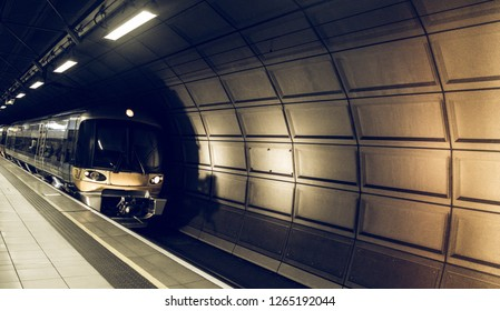 Beautiful railway station interior with modern commuter train at arriving Heathrow airport, London. Railroad with vintage toning for transportation concept