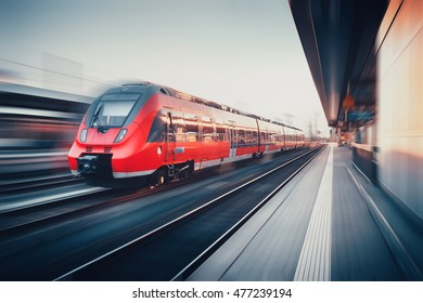 Beautiful railway station with modern high speed red commuter train with motion blur effect at sunset. Railroad. Vintage toning. Railroad travel background, tourism. Industrial