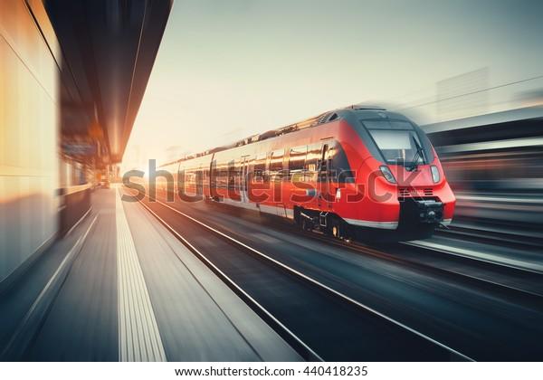 Schöner Bahnhof mit modernem Hochgeschwindigkeits-Pendlerzug mit Bewegungsunschärfe bei buntem Sonnenuntergang in Nürnberg. Eisenbahn mit Vintage-Tönung