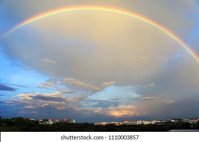 Beautiful rainbow after storm in blue sky and clouds over the city. Amazing natural phenomenon background.