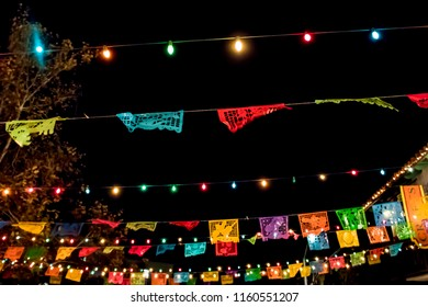 Beautiful Rainbow Colored Paper Flags and Lights Hang across a Day of the Dead Evening Celebration, Horizontal Orientation in San Diego, California, USA