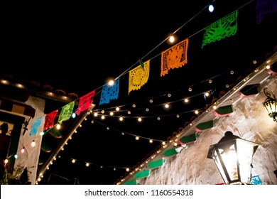 Beautiful Rainbow Colored Paper Flags and Lights Hang across Traditional Adobe and Tile Spanish Colonial Buildings for the Day of the Dead Holiday in San Diego, California, USA