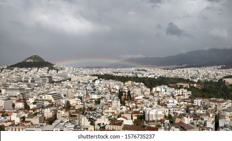 Beautiful rainbow over the big city of Athens on a cloudy day