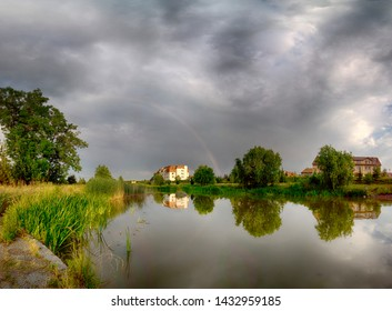 Beautiful rainbow and storm clouds over the lake, on the last day of spring, in Biskupice Podgorne near Wroclaw, Poland.