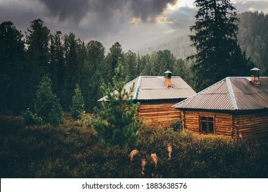 A beautiful rainy rural scenery in the mountains with shallow depth of field and selective focus on two small wooden cabins in deep taiga forest with particles of rain everywhere, dramatic stormy sky