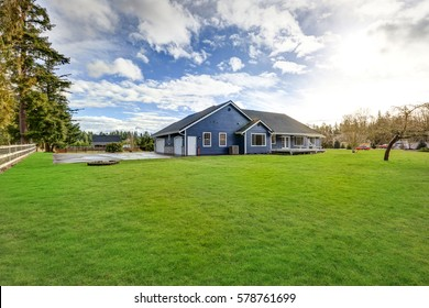 Beautiful rambler house with tile roof, blue siding and well kept lawn in the front yard. Northwest, USA