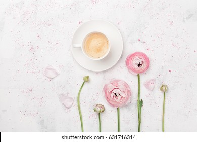 Beautiful ranunculus flowers and cup of coffee on white table from above. Breakfast in pastel color. Flat lay style.