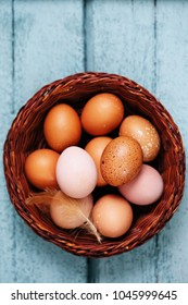 Beautiful raw eggs in basket on a wooden background