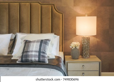 Beautiful reading lamp and flower pot next to bed in luxury interior bedroom