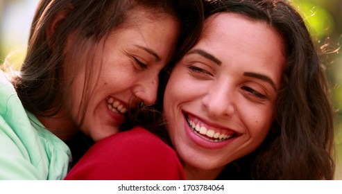 Beautiful real life LGBT women smiling. Lesbian couple embrace, authentic smiles and happiness