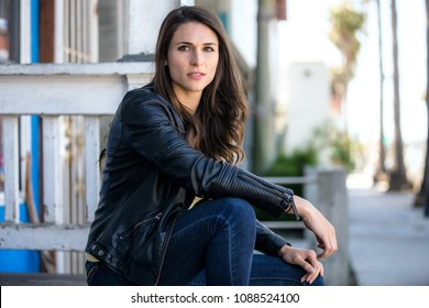 Beautiful rebel rough serious woman looking strong and confident on city street