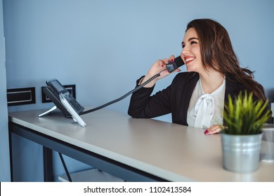 Beautiful receptionist girl talking on the phone and smiling