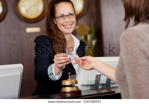 Beautiful receptionist handing over a business card to a customer with a warm welcoming smile