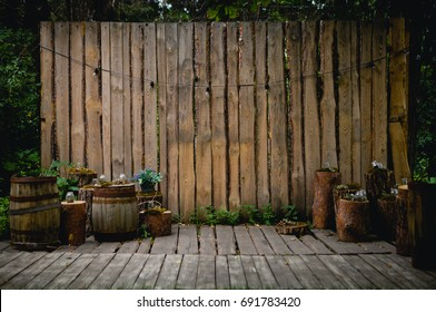 A beautiful recreation area in the park or in the garden. Wooden terrace, rustic loft interior. Retro garland with luminous bulbs, decorated pots with flowers and candles