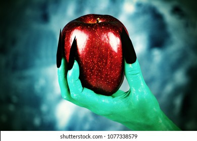 Beautiful red apple in green hands of old witch with black nails.Fairytale scary. mystical and fantasy scene with green hands and red apple.