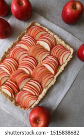 Beautiful red apple lattice tart, on a white baking sheet and light grey background with fresh ripe red apples aside. Apple season, Fall, Holidays, home baking concept, Copy space. Flat lay, top view