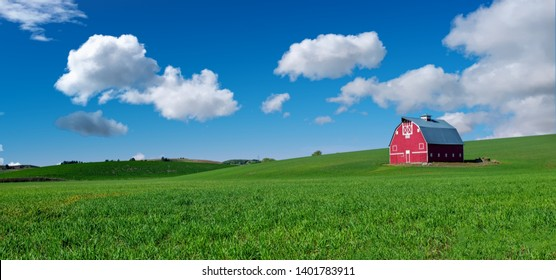 Beautiful red barn with green field and blue sky with clouds