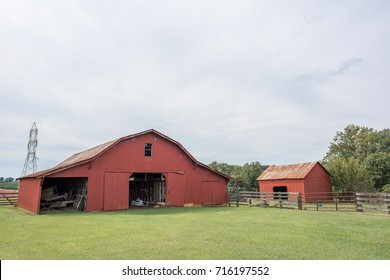 Beautiful red barn in a green, grassy field in rural, upstate South Carolina.