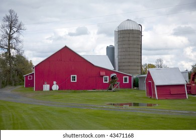 Beautiful red barn, silo and outbuildings just after a heavy rain with puddles in the yard