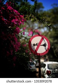 Beautiful red and black colour sign board of do not blow horn or no honking with beautiful bougainvillea flowers. No horn sign board on the street with beautiful background of bougainvillea.