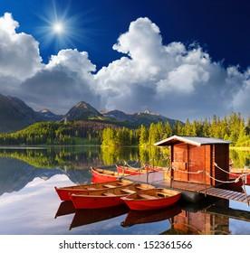Beautiful red boat in a mountain lake Strbske Pleso, Slovakia, Europe