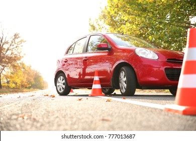 Beautiful red car and safety cones in driving school