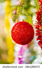 Beautiful red Christmas ball and shining tinsel hanging on branch of tree. Selective focus in foreground, colorful blurry bokeh in background. Close-up of Xmas holiday composition for Happy New Year.
