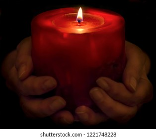 Beautiful red Christmas candle lit in a dark atmosphere, supported by female hands