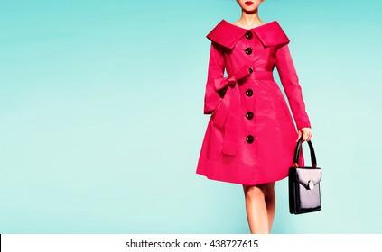 Beautiful red coat woman with black leather handbag. Fall winter fashion image.