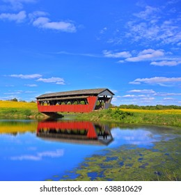A beautiful red covered bridge over a shining pond in Ohio farmland.