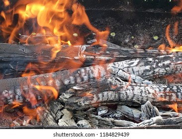 Beautiful red flame from slice wood, dark grey black coals inside metal brazier. Wood burning in the brazier on bright yellow flame. Flames fire preparation for cooking barbecue. Brazier on fires coal