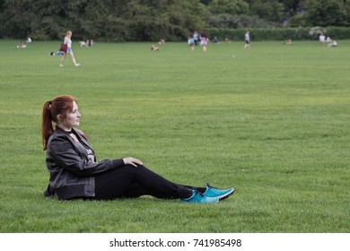 Beautiful red hair ginger smiling girl sitting on grass lawn in park, profile view