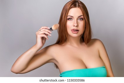 Beautiful red hair plus size model applying make up with a brush on a neutral grey background. Flawless skin, fashion glamour portrait