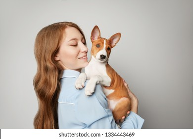Beautiful red haired girl embracing puppy on white background. Studio portrait of white appealing woman chilling with dog.