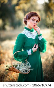 Beautiful red haired girl in green long vintage dress and basket of flowers standing in park.Pretty tenderness model with perfect hairstyle dreaming and looking at camera.Art work and fairytale