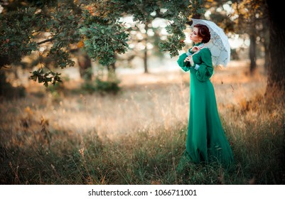 Beautiful red haired girl in green long vintage dress and lace umbrella standing near park.Pretty tenderness model with perfect hairstyle dreaming and looking afar.Art work and fairytale