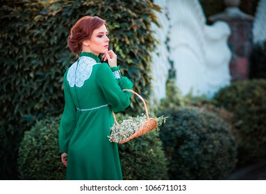 Beautiful red haired girl in green long vintage dress and basket of flowers standing near fence.Pretty tenderness model with perfect hairstyle dreaming and looking afar.Art work and fairytale