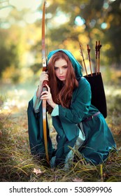 Beautiful red haired girl in green long medieval dress with hood  sitting on a grass. Art work of brave heart woman with bow and arrows. Fairy tale story.Glowing sun.Colorful background.