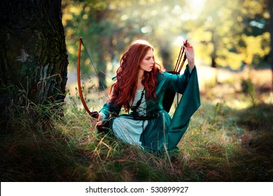 Beautiful red haired girl in green  medieval dress is going to shoot with arrows and looking afar . Fairy tale story about brave heart woman .Glowing sun on archer. Warm art work.