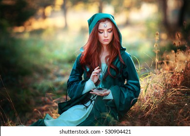 Beautiful red haired girl in green medieval dress with hood holding a sand glass and looking down.Fairy tale story about brave heart woman.Warm art work