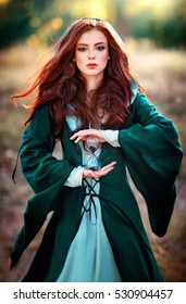 Beautiful red haired girl in green medieval dress in a hood holding a sand glass and looking at camera. Fairy tale story about brave heart woman.Warm art work