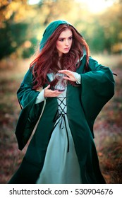 Beautiful red haired girl in green medieval dress in a hood holding a sand glass and looking afar.Fairy tale story about brave heart woman.Warm art work