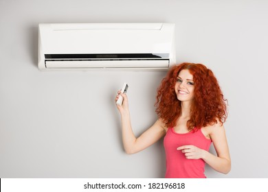 Beautiful red haired girl holding a remote control air conditioner.