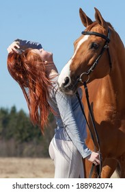 Beautiful red haired girl and red horse