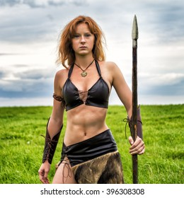 Beautiful red - haired girl in the image of ancient warriors on the background summer nature. Evening.