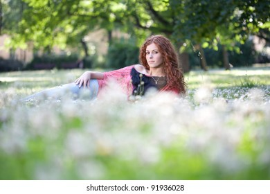 Beautiful red haired girl laying on the green grass and flowers