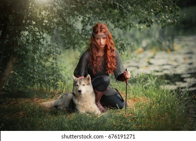 Beautiful red haired girl in metal medieval armor dress with swords sitting in warlike pose near river with water lilies. Fairy tale story about warrior with dog . Glowing light. Warm art work.