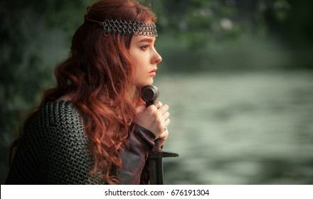 Beautiful red haired girl in metal medieval armor dress with sword standing in warlike pose and looking afar with fearless. Fairy tale story about warrior . Warm art work.