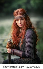 Beautiful red haired girl in metal medieval armor dress with sword standing in warlike pose and looking at camera with fearless. Fairy tale story about warrior . Warm art work.